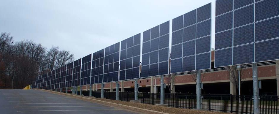 Pole mounted solar array along parking lot edge.